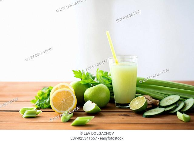 healthy eating, food, dieting and vegetarian concept - glass of green juice with fruits and vegetables on wooden table