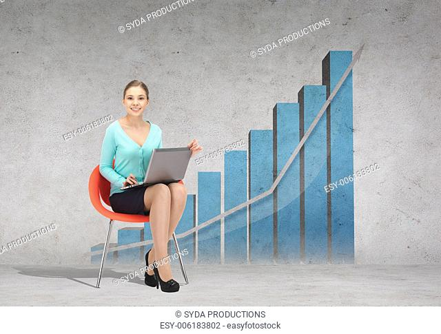 business, office and technology concept - young businesswoman sitting in chair with laptop