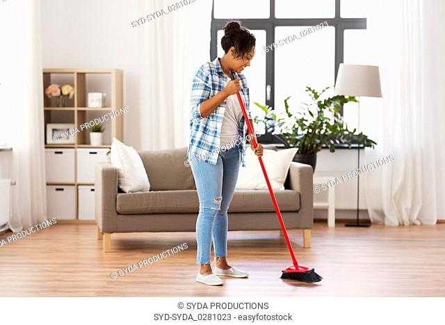 woman with sweeping broom brush cleaning floor