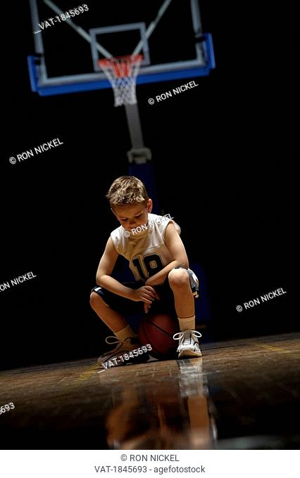 Young boy sitting on basketball court looking solemn