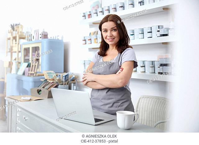 Portrait confident, smiling art shop business owner standing at counter
