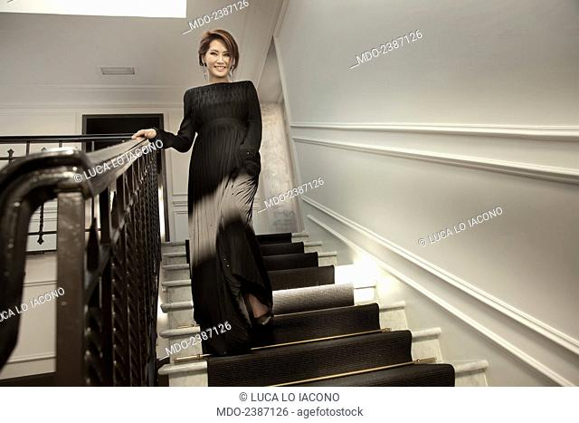 The beautiful Chinese Canadian actress and soprano Lu Ye walking down a staircase in an elegant dress designed by Giorgio Armani for the Christmas concert in...