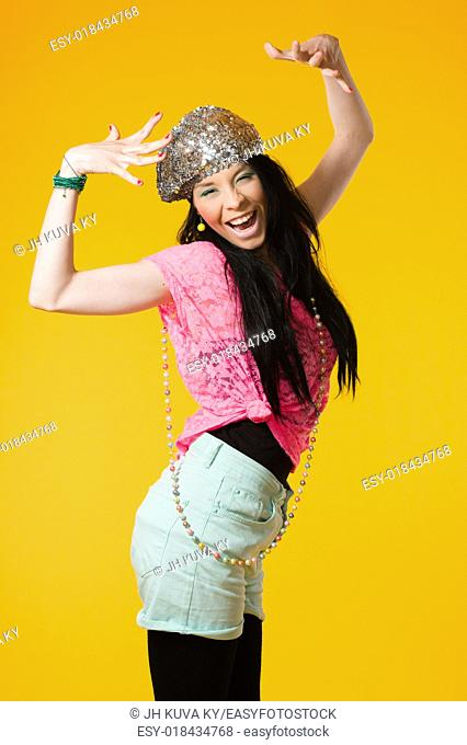 Beautiful expressing girl wearing colorful clothes, yellow background