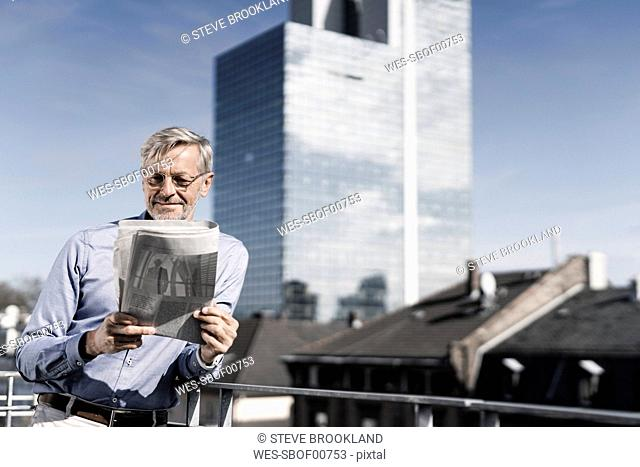 Grey-haired man on balcony reading newspaper