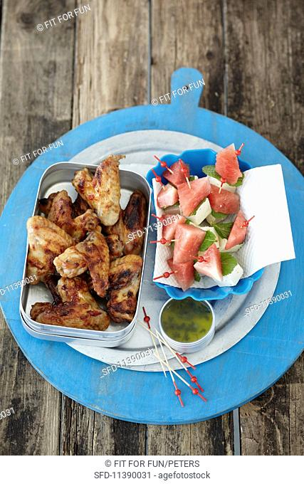Spicy marinated chicken wings and sheep's cheese and melon kebabs
