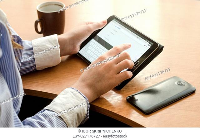 Girl in shirt sitting with a tablet. Sitting at the table, on the table cup and a smartphone