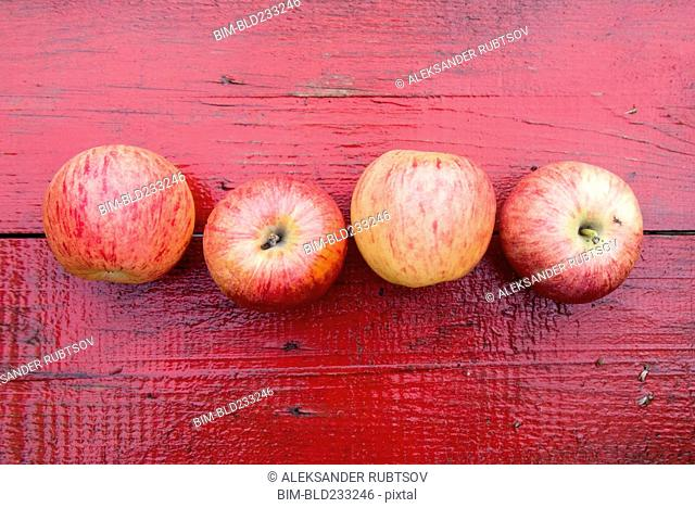 Close up of row of red apples on red wooden table