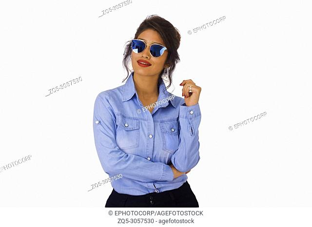 Stylish woman in blue top, wearing goggles smiling with and raised arm. Front pose