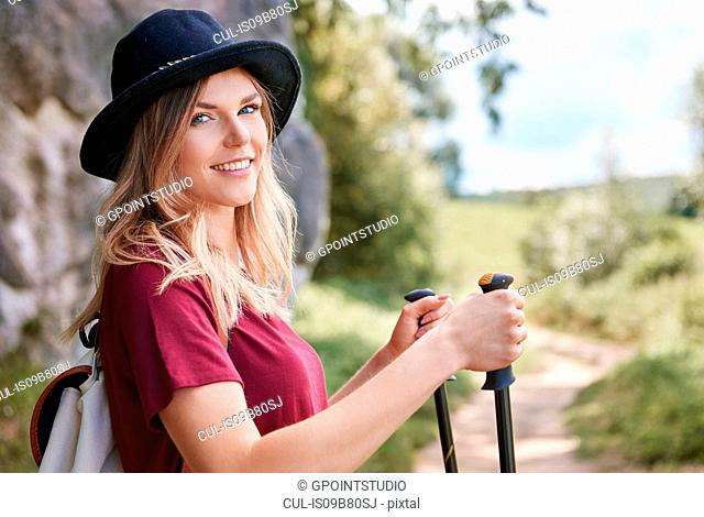 Portrait of woman with walking poles looking at camera smiling, Krakow, Malopolskie, Poland, Europe