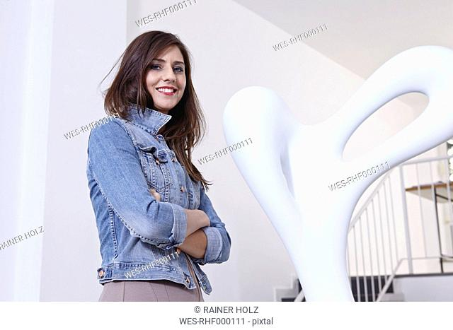 Germany, Cologne, Mid adult woman standing near sculpture in art gallery, smiling, portrait