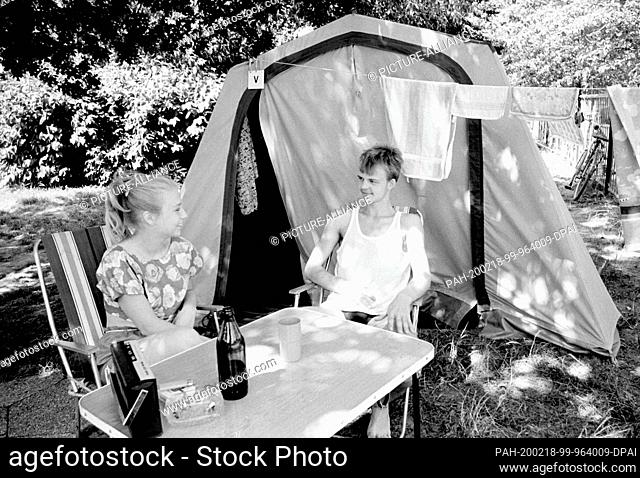 07 July 1989, Saxony, Torgau: A girl and a boy are sitting in front of a tent on a camping site near Torgau in the summer of 1989