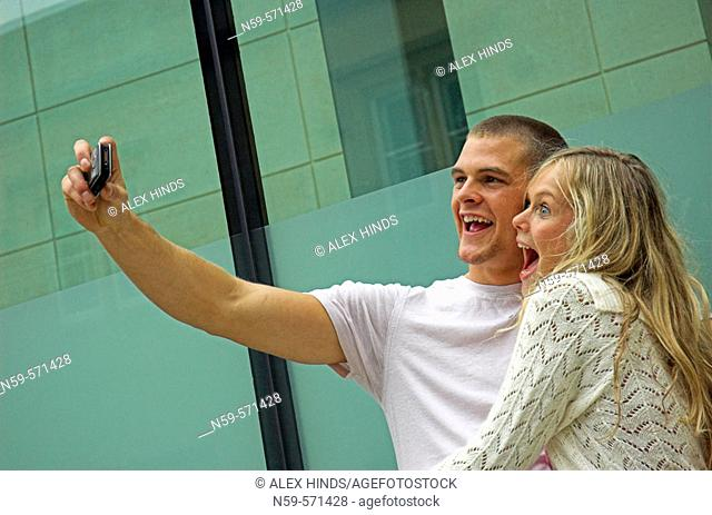 Attractive young couple playing with a cell phone camera. The boyfriend is photographing himself with his girlfriend
