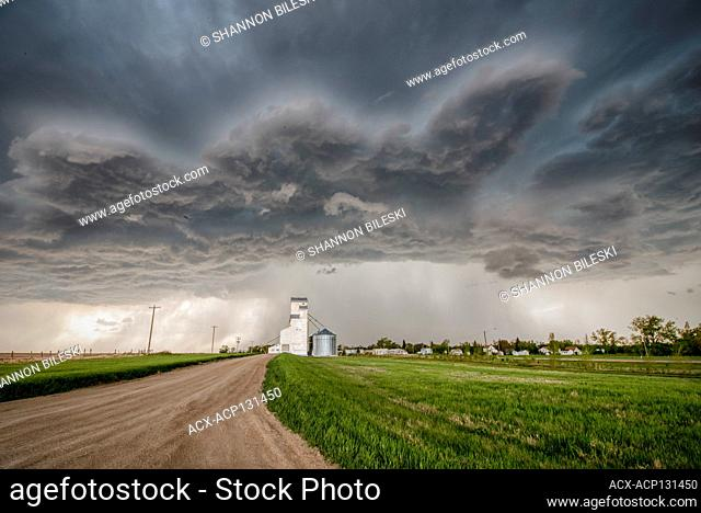 Storm with gravel road over grainery in rural southern Manitoba Canada