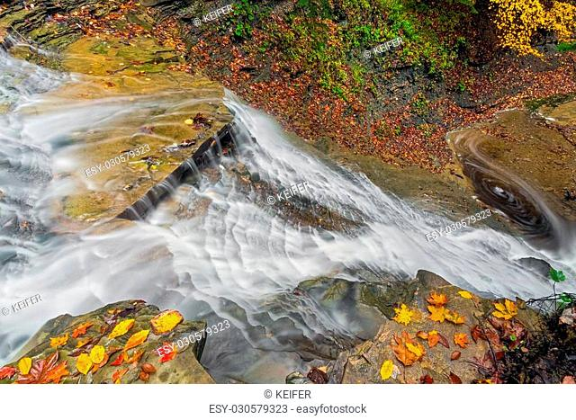 Buttermilk Falls, a waterfall in Ohio's Cuyahoga Valley National Park, cascades down rock ledges with colorful autumn leaves