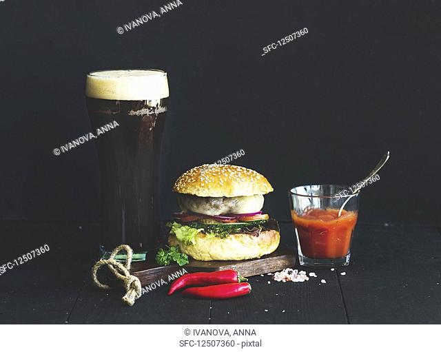 Fresh homemade burger on wooden serving board with spicy tomato sauce, sea salt, herbs and glass of dark beer over black background