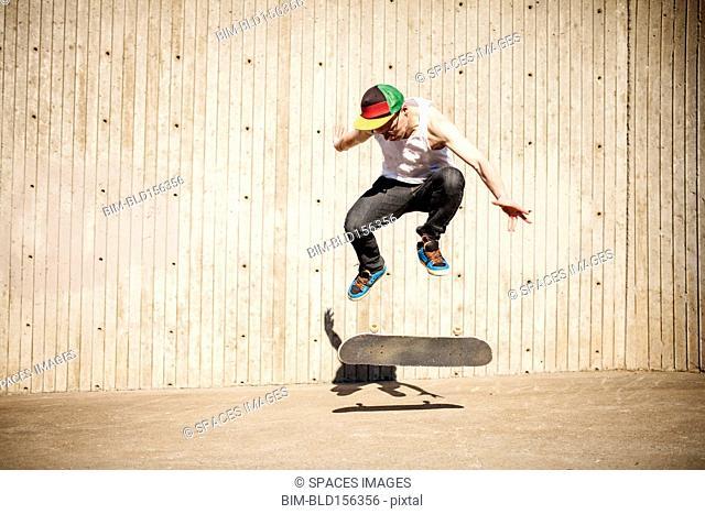 Caucasian man doing skate trick near wooden wall