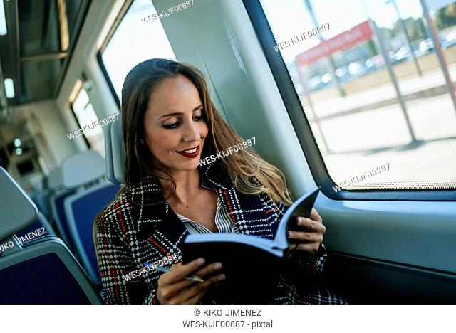 Businesswoman on a train with notebook