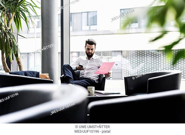 Businessman sitting in lobby, drinking coffee, reading documents