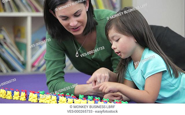Teacher and female pupil lying on the floor using colored platic bears to count.Shot on Canon 5d Mk2 with a frame rate of 30fps