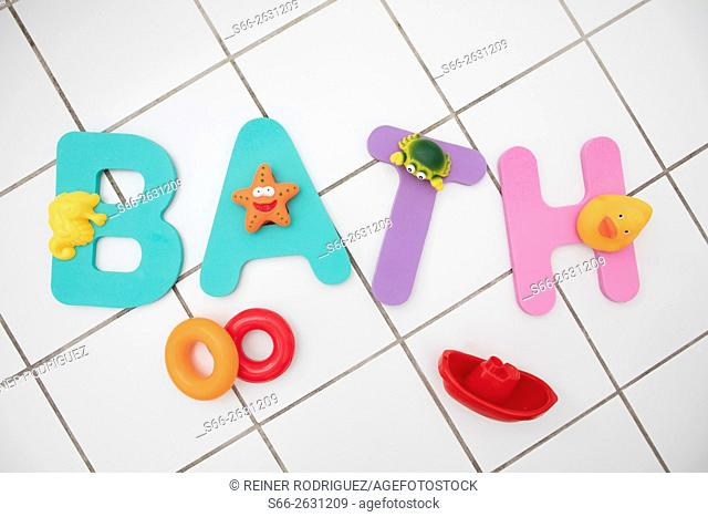 The word BATH made of letters from a children's mat with a selection of bath tub toys