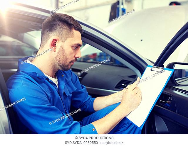 auto mechanic man with clipboard at car workshop