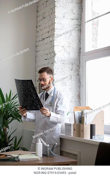 Closeup portrait of intellectual man healthcare personnel with white labcoat, looking at brain x-ray radiographic image, ct scan, mri, clinic office background