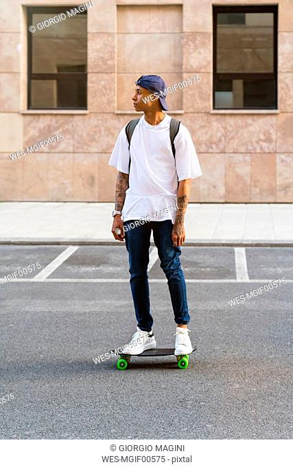 Tattooed young man standing on skateboard looking at distance