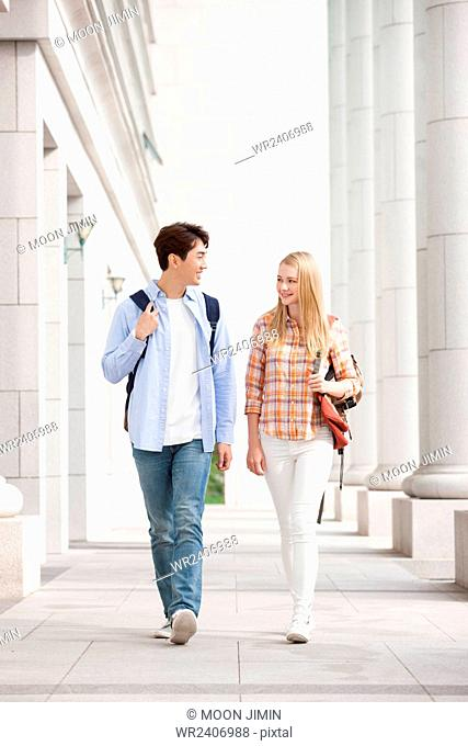 International student and a domestic student walking together at campus building outside with a smile