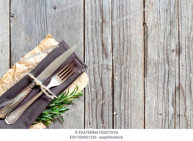 Vintage Table setting with rosemary decor on old wooden table