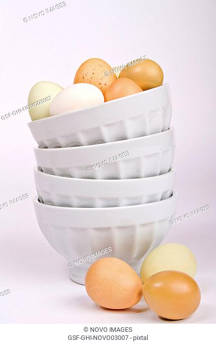 Assortment of Eggs on Top of and Next to a Stack of Bowls