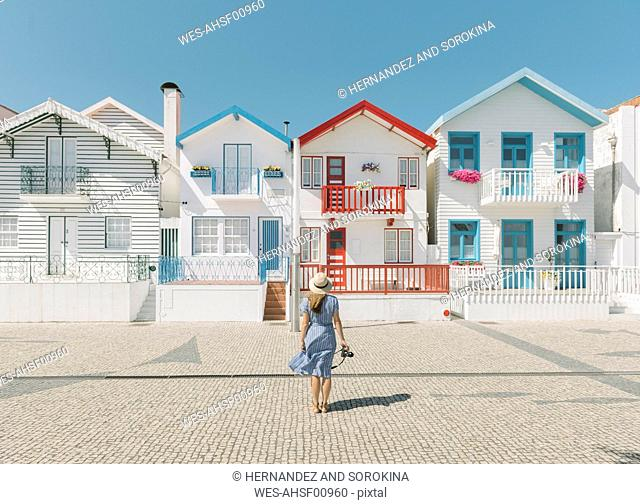 Rear view of woman with camera in front of houses, Costa Nova, Portugal