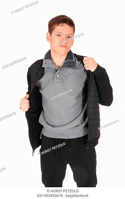 A close up image of a young teenager boy standing isolated for white .background in the studio, taking his jacket of