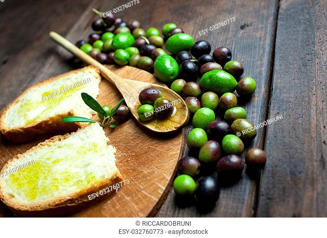 olive oil and bread on wooden table