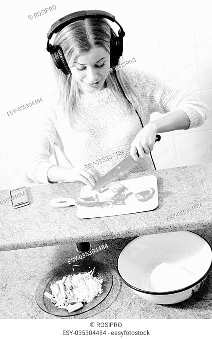 black and white closeup portrait of making pizza cheerful beautiful blond young woman having fun relaxing with headphones listening to music