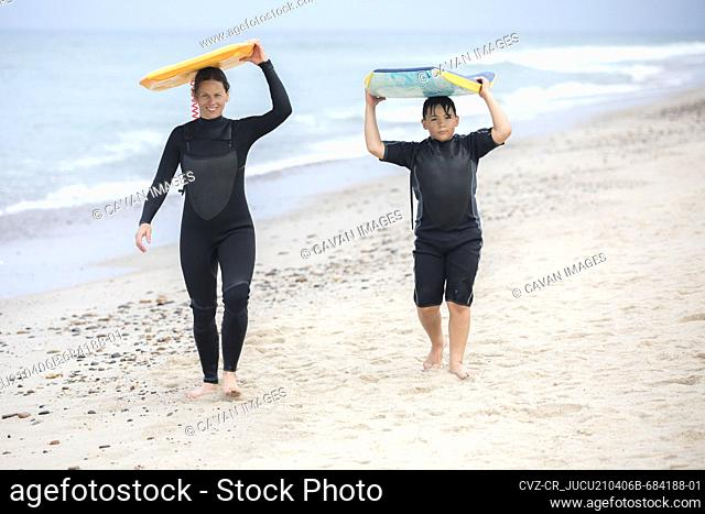 mother and son in wetuits walking down beach carrying boogie boards