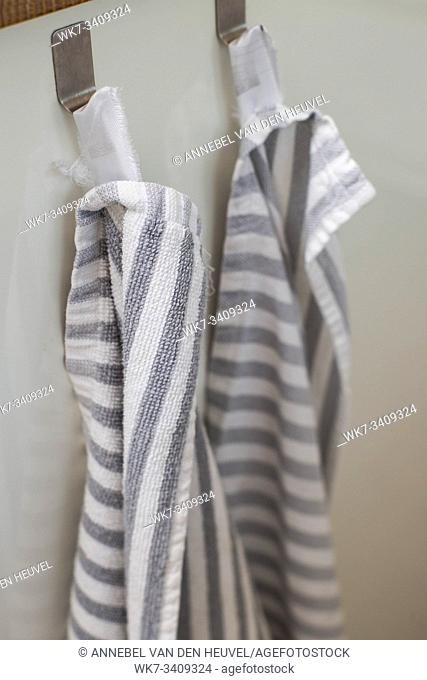 Two kitchen towels hanging on a hooks in a kitchen close-up modern