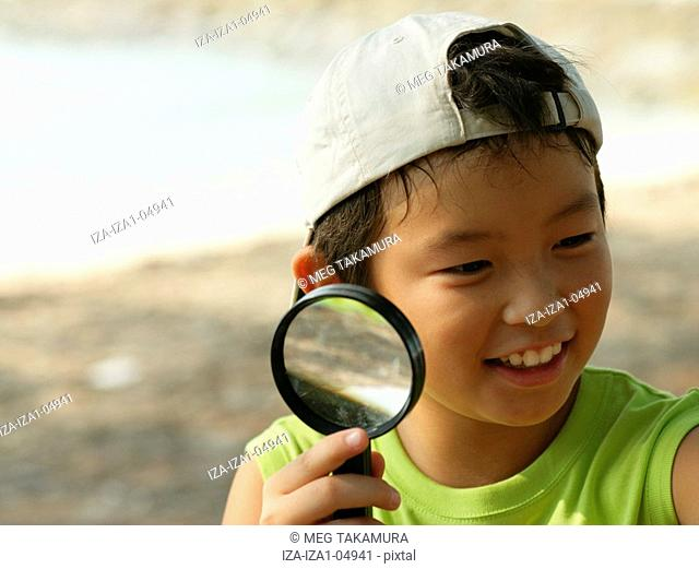 Close-up of a boy holding a magnifying glass and smiling