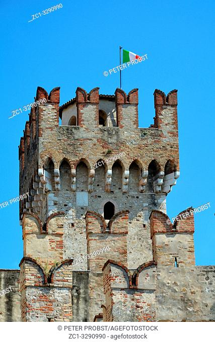 Scaligero Castle in a detail view with the Italian flag in the historic center of Sirmione at Lake Garda - Italy