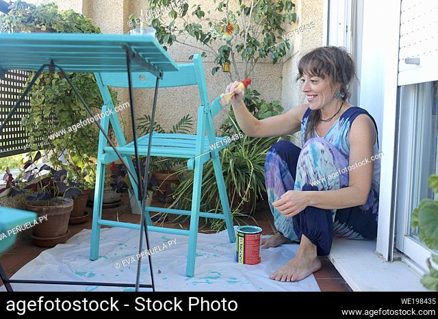 Young woman painting a chair green on her terrace