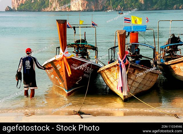 Local man standing by longtail boats at Ao Loh Dalum beach on Phi Phi Don Island, Krabi Province, Thailand. Koh Phi Phi Don is part of a marine national park
