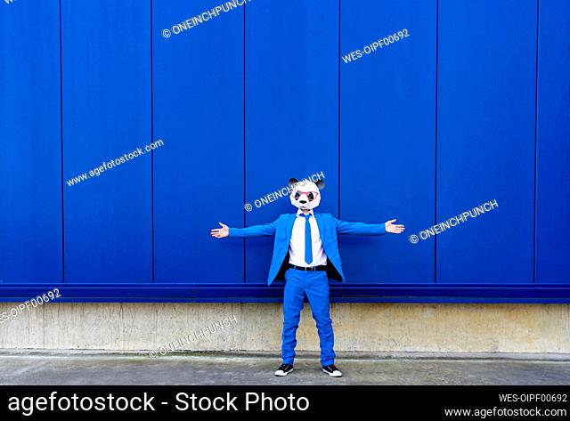 Man wearing vibrant blue suit and panda mask standing outdoors with open arms