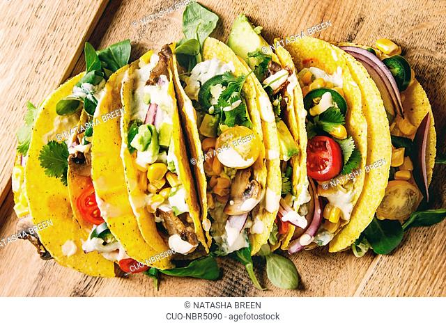Variety of vegetarian corn tacos with vegetables, green salad, chili pepper served on wooden tray with cream sauce. Top view, close up