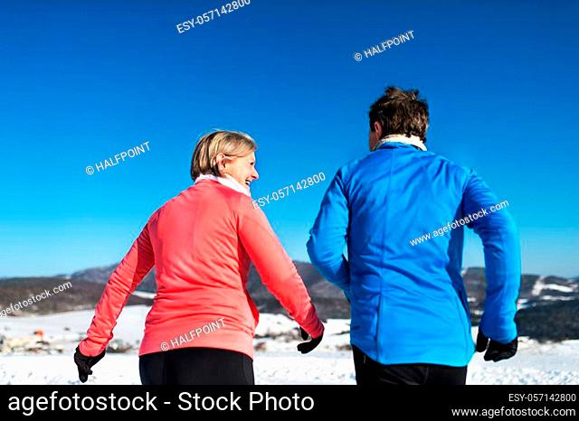 Rear view of senior couple jogging in snowy winter nature
