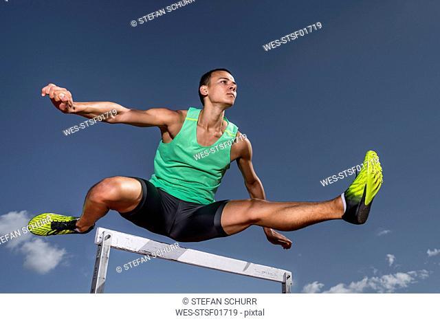 Young runner crossing hurdle