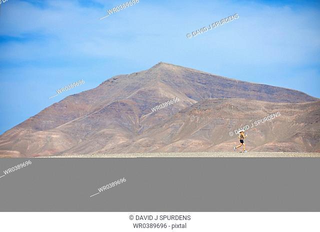 A long distance female runner jogging through an arid mountainous desert