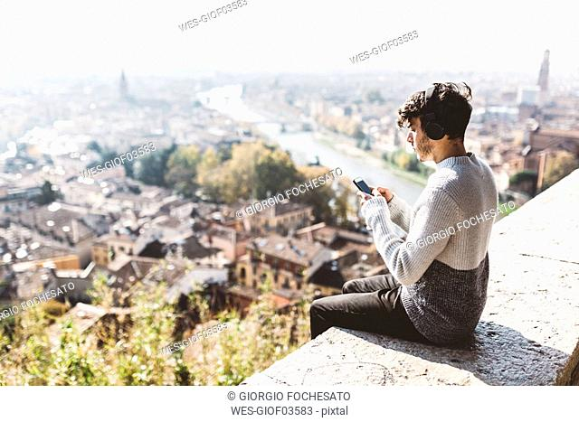 Italy, Verona, tourist using smartphone, headphones