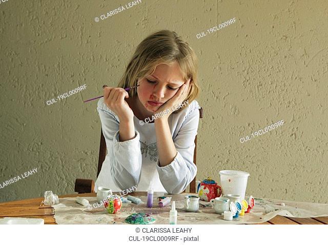 Girl painting china tea set