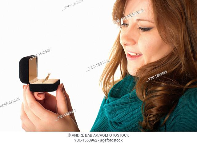 Young woman looking at diamond ring in jewelry gift box