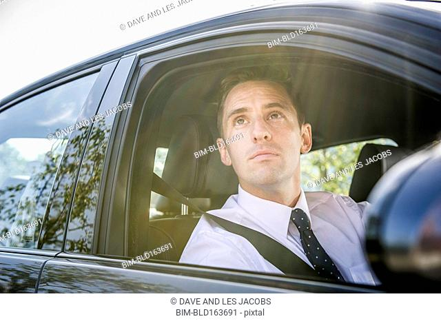Caucasian businessman looking out car window