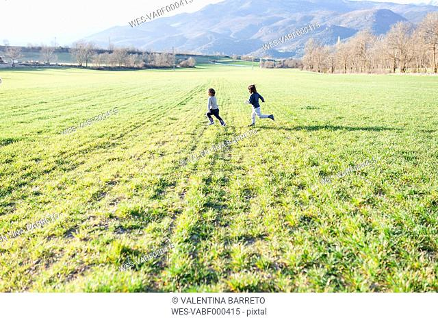 Two boys running in a field